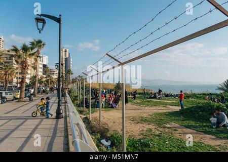 Famiglie giocare sull'erba per la spiaggia in un bel pomeriggio di sole in una zona che una volta era recintata Foto Stock