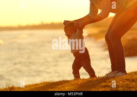 Retroilluminazione silhouette di un fiducioso il bambino ad imparare a camminare e di sua madre aiutare lui al tramonto Foto Stock