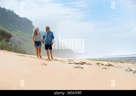 Affettuosa coppia senior camminando sul , tenendo le mani Foto Stock