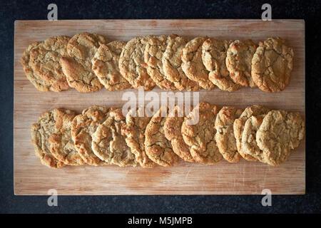 Due righe di cucinata fresca pianura American cookie biscotti steso a raffreddare su una tavola di legno. Foto Stock