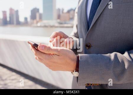 Imprenditore utilizzando il suo telefono cellulare su un tetto in città Foto Stock