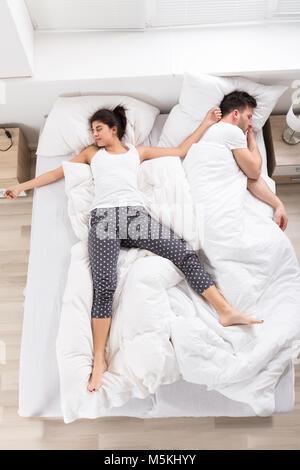 Vista aerea della giovane donna che dorme accanto a suo marito sul letto Foto Stock