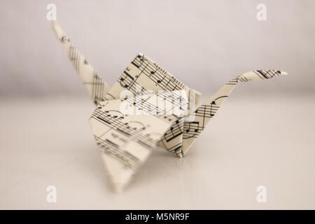 Gru fatta di carta da musica, piegato con la vecchia tecnica di origami. Foto Stock