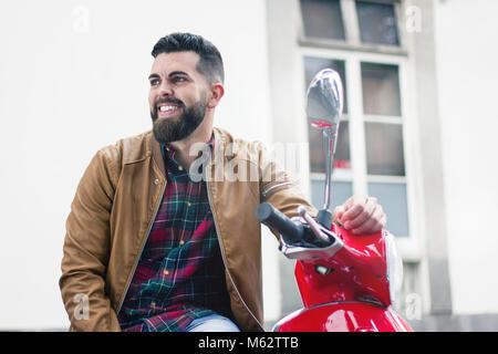 Felice giovane uomo seduto sul motociclo rosso indossando giacca di pelle marrone in città. Hipster con barba folta Foto Stock