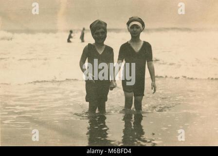 Antique c1900 fotografia, due giovani bambini nel periodo Vittoriano costumi da bagno all'oceano. Posizione sconosciuta, Foto Stock