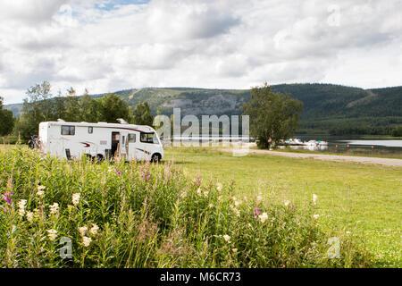 Grandi camper parcheggiato su erba verde vicino a un lago in Scandinavia. Foto Stock