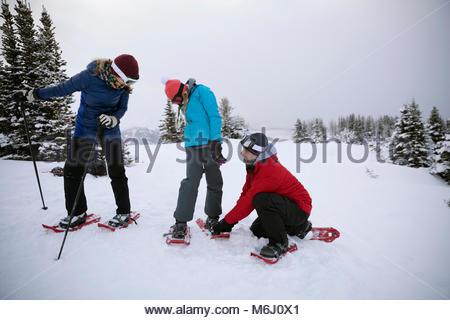 Preparazione della famiglia, mettendo su racchette da neve in neve Foto Stock