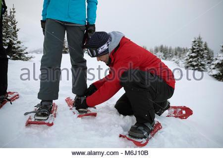 Padre aiutando la figlia messo con le racchette da neve nella neve Foto Stock