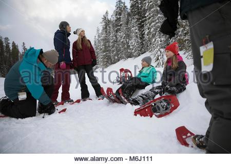 Famiglia preparando per escursioni con le racchette da neve, mettendo su racchette da neve in neve Foto Stock