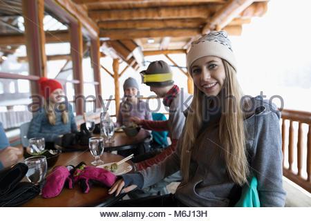 Ritratto sorridente, fiducioso ragazza adolescente sciatore di mangiare con la famiglia apres-ski in ski resort Foto Stock