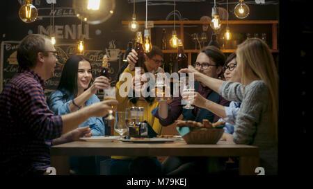 Diversi gruppi di amici festeggiare con un brindisi e il Clink sollevato bicchieri con bevande varie nella celebrazione. Foto Stock
