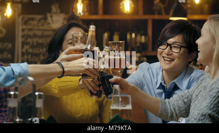 Gruppo diversificato di splendidi giovani fare un brindisi e Clink sollevato bicchieri con bevande varie nella celebrazione. Foto Stock
