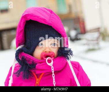 Toddler adorabile bambina in un magenta tuta da neve giocando sulla neve. Foto Stock