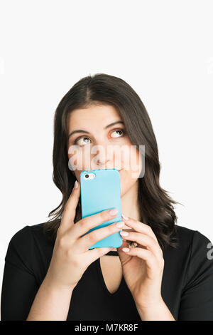Una donna che mantiene il suo smart device e cercando pensieroso. Foto Stock