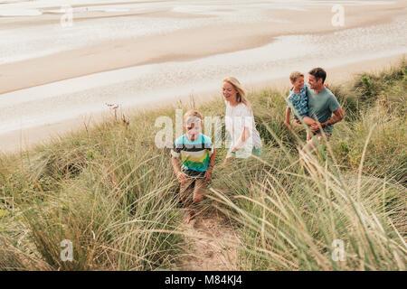 Angolo di alta vista di una famiglia a piedi attraverso le dune di sabbia. Foto Stock