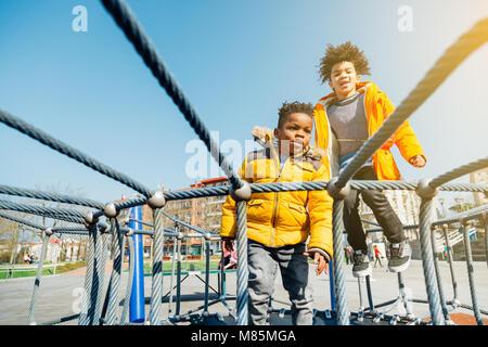 Due bambini con giallo cappotti di saltare sul letto di elastico in un parco giochi in una giornata di sole Foto Stock
