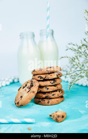 Cookie di cioccolato con un organico di bottiglie di latte vicino a fiore su sfondo blu. Una sana prima colazione Foto Stock