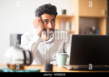 Ritratto di imprenditore pensando alla scrivania nel suo ufficio Foto Stock