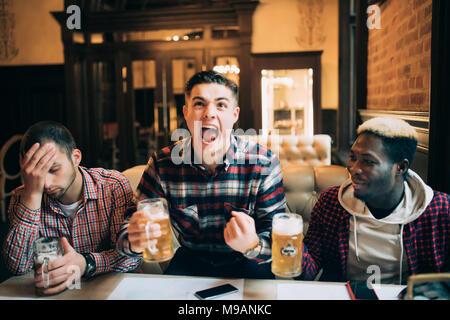Guardare la TV in bar. Due giovani felici gli uomini a bere birra e gesticolando mentre è seduto in bar Foto Stock