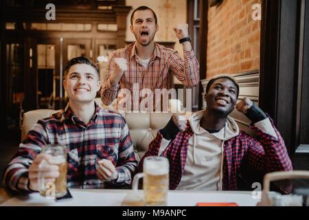 Gli uomini presso il pub watcing del gioco del calcio e di bere birra. Foto Stock