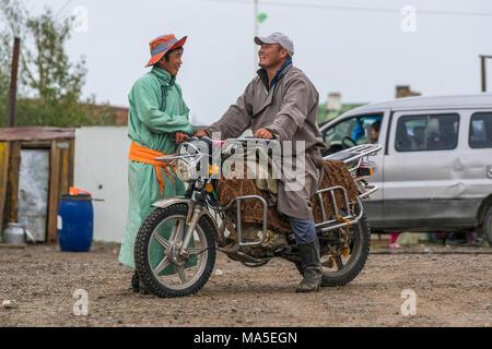 Un uomo su una moto in chat con un altro uomo. Huzirt, Sud provincia Hangay, Mongolia. Foto Stock