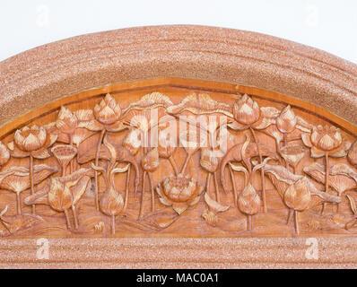 Lotus incisioni sul bordo di teak che si trova sulla parete sopra la porta della chiesa. Foto Stock