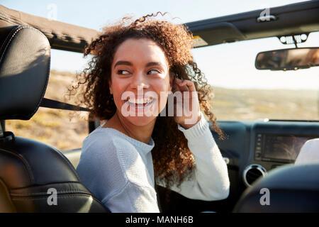 Giovane donna girando nel sedile passeggero anteriore di un automobile Foto Stock