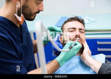 Dentista esaminando i denti del paziente nella sua clinica Foto Stock
