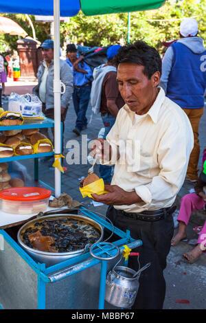 Píllaro, ECUADOR - Febbraio 6, 2016: uomo non identificato vende sweet fichi sulla strada per la festa di diabladas di Pillaro Foto Stock