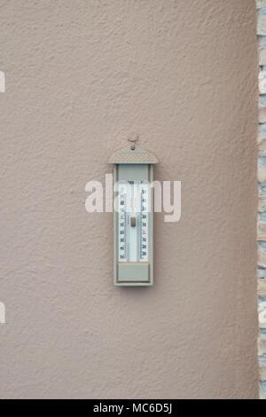 Vintage termometro analogico appeso a una parete. Foto Stock