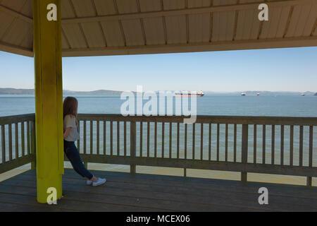 Una giovane ragazza adolescente sta appoggia contro un pilastro di sostegno su un oggetto ponte di osservazione che guarda fuori le navi nel fiume Columbia in Astoria, Oregon Foto Stock