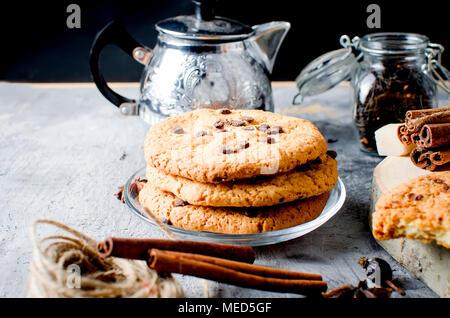 Biscotti con gocce di cioccolato, сup di caldo tè nero, cannella, anice su sfondo scuro, spezie per il tè. Foto Stock