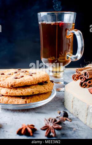 Pila di biscotti con gocce di cioccolato, сup di caldo tè nero, cannella, anice su sfondo scuro, spezie per il tè. Foto Stock