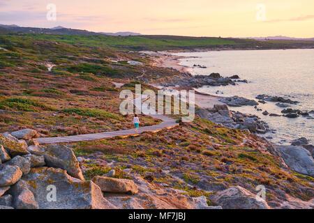 L'Italia, Sardegna, Lu Litarroni, senior Donna che cammina sulla passerella in legno al tramonto Foto Stock