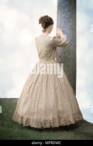 Una donna in un periodo il vestito è appoggiata contro un pilastro Foto Stock