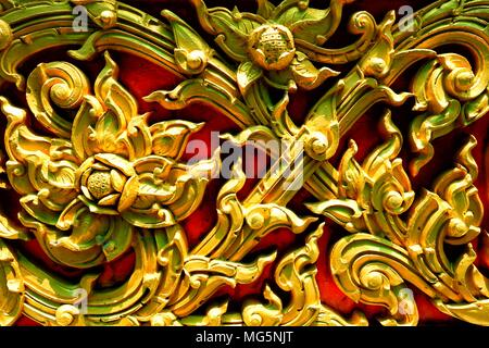 Chiuso-up Vintage Golden scultura tailandese sul muro di pietra. Foto Stock