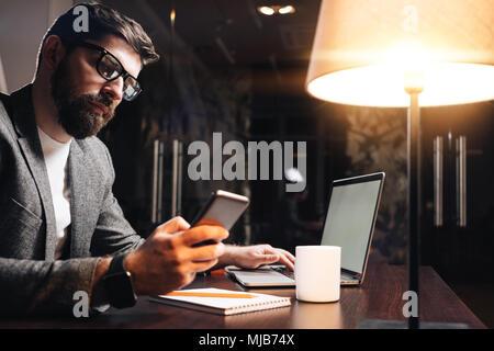 Barbuto imprenditore con laptop tramite il telefono cellulare alla notte loft ufficio. Giovane uomo la digitazione del testo su smartphone contemporanea. Processo di lavoro a cowork Foto Stock