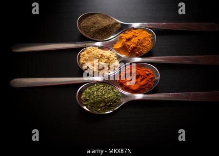 Spezie colorate in argento cucchiai, collocato su un tavoli in legno nero. Peperoncino, pepe, sale, basilico, senape Foto Stock