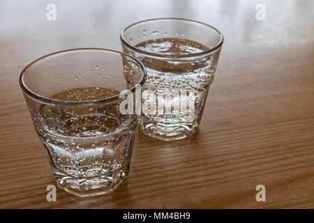 Due appena spillata bicchieri di acqua frizzante isolati su legno. Foto Stock