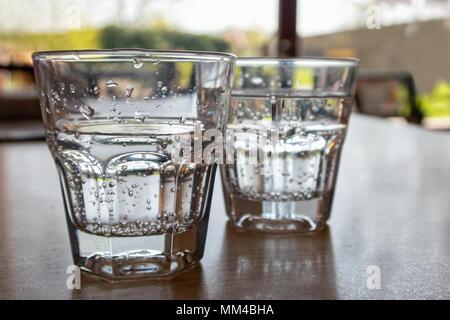 Due appena spillata bicchieri di acqua frizzante sul tavolo di legno. Foto Stock