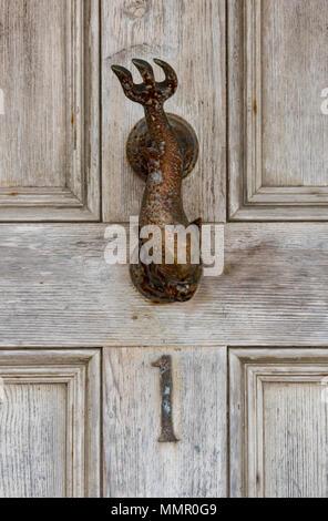Una tradizionale porta in ottone respingente nella forma di un pesce o di una creatura marina su un ingresso ad una casa in st Ives in Cornovaglia. Marittima nautico. Foto Stock