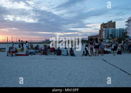 Un folto gruppo di persone che guardano uomo squadra giocare pallavolo sulla spiaggia al tramonto. Gli adolescenti società presso la spiaggia. Giocatore di volleyball jumping, kick ball. Foto Stock