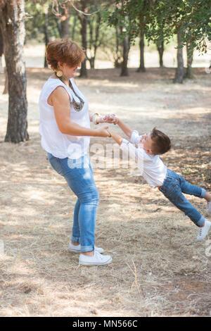 Madre figlio oscillanti da mani nel parco Foto Stock