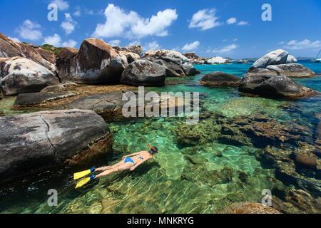 Giovane donna snorkeling in turchesi acque tropicali tra enormi massi di granito presso le Terme zona spiaggia, Isole Vergini Britanniche, Isole dei Caraibi Foto Stock
