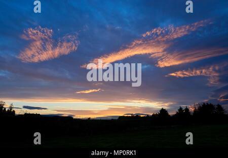 Un drammatico inizio estate tramonto sulla costa nord-est della Scozia, con multi strato nuvole, alcuni dei quali si stanno trasformando in rosso da soli raggi. La Scozia. Foto Stock