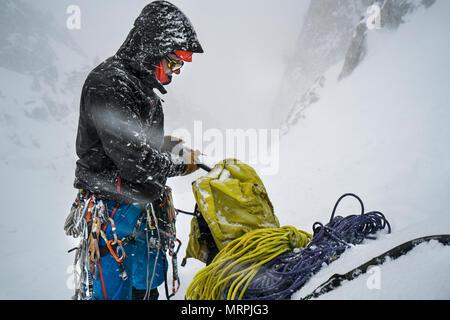 Un uomo confezioni la sua marcia di distanza alla fine della giornata di arrampicata su ghiaccio Foto Stock