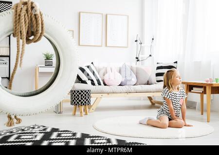Bimba bionda seduta sul pavimento di tendenza scandinavo camera bianca Foto Stock