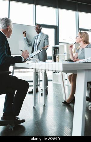 African American businessman scrivere sulla lavagna e guardando i colleghi al business meeting Foto Stock