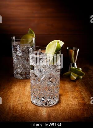 Riflettori puntati su due bicchieri di cristallo pieno di gin tonic cocktail, con un calce guarnire, girato su un antico tavolo di legno alto. Foto Stock