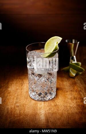 Riflettori puntati su un cristallo di bicchieri pieni di gin tonic cocktail, con un calce guarnire, girato su un antico tavolo di legno alto. Foto Stock